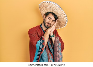 Young hispanic man holding mexican hat sleeping tired dreaming and posing with hands together while smiling with closed eyes.