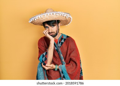 Young hispanic man holding mexican hat thinking looking tired and bored with depression problems with crossed arms.