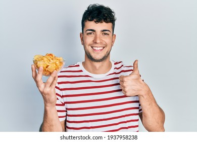 Young hispanic man holding potato chip smiling happy and positive, thumb up doing excellent and approval sign