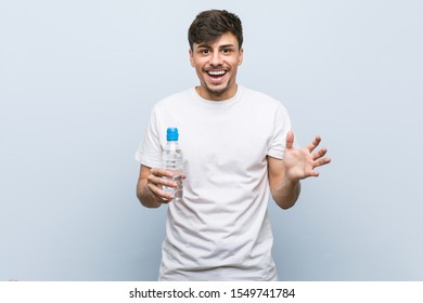 Young hispanic man holding a water bottle celebrating a victory or success