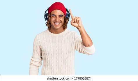 Young hispanic man listening to music using headphones pointing finger up with successful idea. exited and happy. number one.