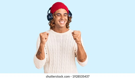 Young hispanic man listening to music using headphones very happy and excited doing winner gesture with arms raised, smiling and screaming for success. celebration concept.