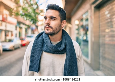 Young hispanic man with serious expression wearing scarf walking at the city.