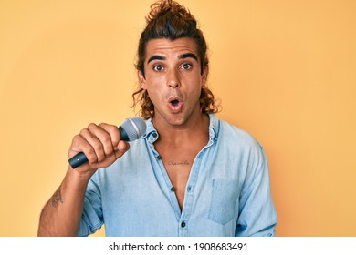 Young hispanic man singing song using microphone scared and amazed with open mouth for surprise, disbelief face