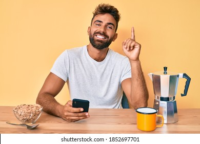 Young hispanic man sitting on the table having breakfast and using smartphone surprised with an idea or question pointing finger with happy face, number one