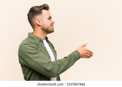 young hispanic man smiling, greeting you and offering a hand shake to close a successful deal, cooperation concept against isolated background