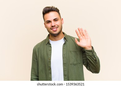 young hispanic man smiling happily and cheerfully, waving hand, welcoming and greeting you, or saying goodbye against isolated background