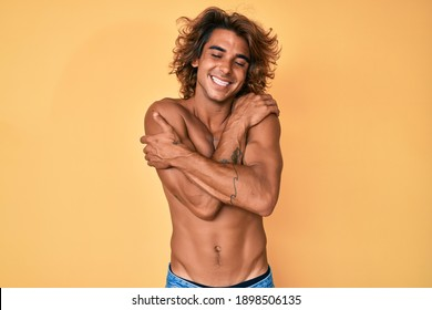Young hispanic man standing shirtless hugging oneself happy and positive, smiling confident. self love and self care