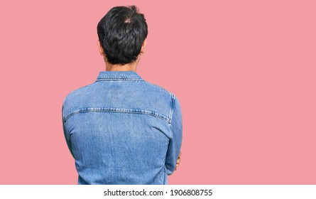 Young hispanic man wearing casual clothes standing backwards looking away with crossed arms