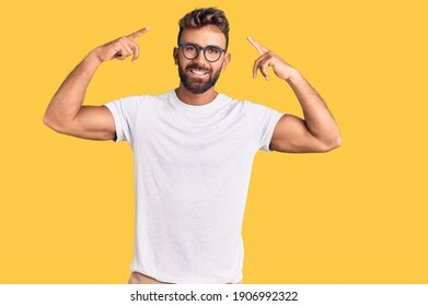 Young hispanic man wearing casual clothes and glasses smiling pointing to head with both hands finger, great idea or thought, good memory