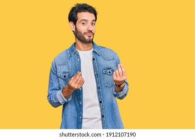 Young hispanic man wearing casual clothes doing money gesture with hands, asking for salary payment, millionaire business