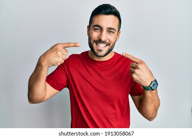 Young hispanic man wearing casual clothes smiling cheerful showing and pointing with fingers teeth and mouth. dental health concept.