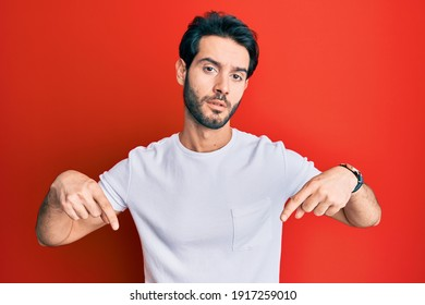 Young hispanic man wearing casual white tshirt pointing down looking sad and upset, indicating direction with fingers, unhappy and depressed.
