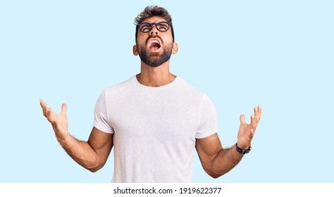 Young hispanic man wearing casual clothes and glasses crazy and mad shouting and yelling with aggressive expression and arms raised. frustration concept.