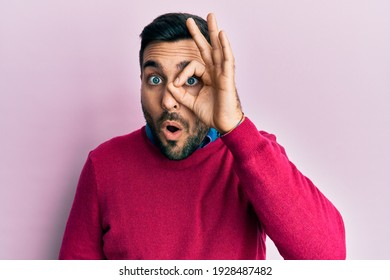 Young hispanic man wearing casual clothes doing ok gesture shocked with surprised face, eye looking through fingers. unbelieving expression.
