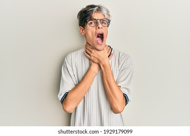 Young hispanic man wearing casual clothes and glasses shouting and suffocate because painful strangle. health problem. asphyxiate and suicide concept.