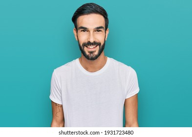 Young hispanic man wearing casual white t shirt with a happy and cool smile on face. lucky person.