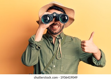 Young hispanic man wearing explorer hat holding binoculars smiling happy and positive, thumb up doing excellent and approval sign