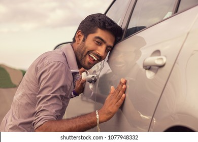 Young hispanic man wearing in formal shirt holding is petting his car and smiling outdoors. A new car, new driver concept