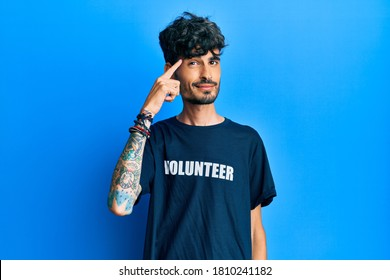 Young hispanic man wearing volunteer t shirt smiling pointing to head with one finger, great idea or thought, good memory