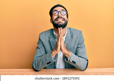 Young hispanic man working at the office begging and praying with hands together with hope expression on face very emotional and worried. begging.