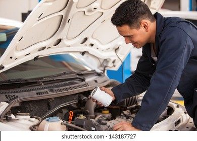 Young Hispanic mechanic changing the oil filter of a car at an auto shop