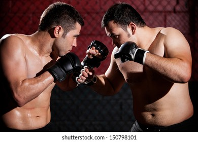 Young Hispanic mixed martial arts fighters during a fight in a cage