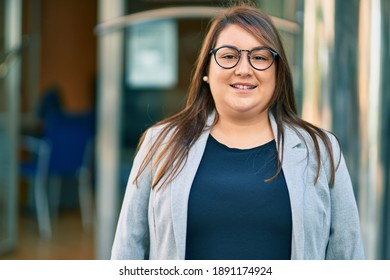 Young hispanic plus size businesswoman smiling happy standing at the city.