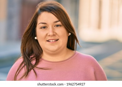Young hispanic plus size woman smiling happy standing at the city.