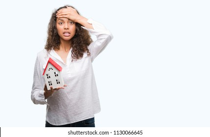 Young hispanic real state agent woman holding small house stressed with hand on head, shocked with shame and surprise face, angry and frustrated. Fear and upset for mistake.