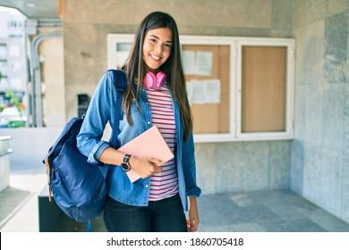 Young hispanic student girl smiling happy using headphones at the university.