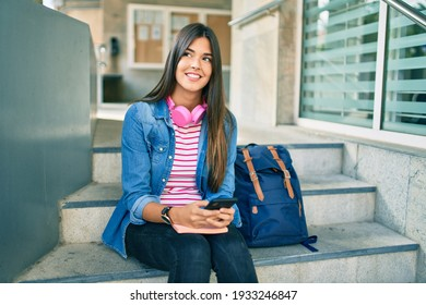 Young hispanic student girl smiling happy using smartphone at the university.