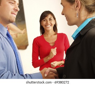 Young hispanic and successful businesspeople shake hands.