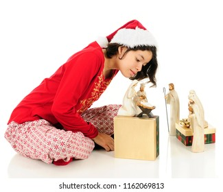 A young Hispanic teen in her pajamas checking out the Christ child in her Nativity set.  On a white background.