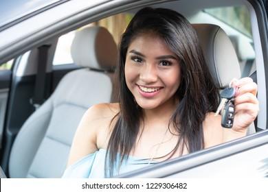 Young hispanic teenage girl learning to drive a car