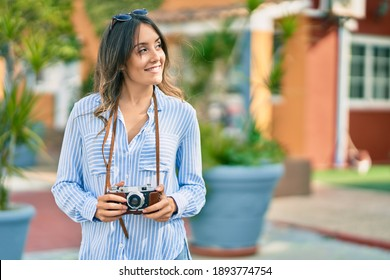 Young hispanic tourist woman smiling happy using vintage camera at the city. - Shutterstock ID 1893774754