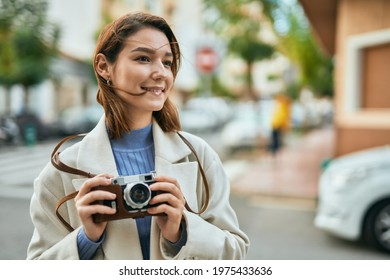 Young hispanic tourist woman smiling happy using vintage camera at the city - Shutterstock ID 1975433636