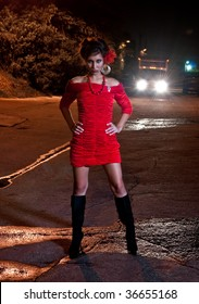 Young hispanic woman in a alley at night while a truck is passing by.