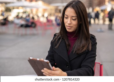 Young Hispanic woman in city using tablet computer