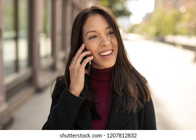 Young Hispanic woman in city walking talking on cell phone