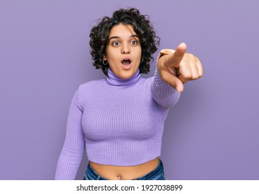 Young hispanic woman with curly hair wearing casual clothes pointing with finger surprised ahead, open mouth amazed expression, something on the front
