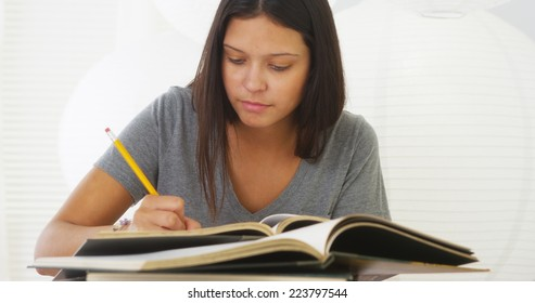 Young Hispanic woman doing research on desk