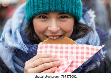 Young Hispanic woman eating local waffle in market in Utrecht, Netherlands.