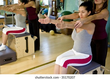 Young hispanic woman and her trainer doing pilates in a gym