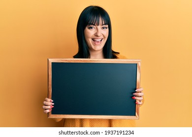 Young hispanic woman holding blackboard smiling and laughing hard out loud because funny crazy joke.