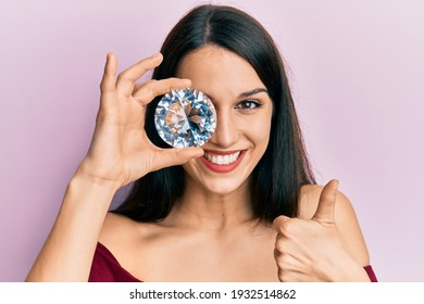 Young hispanic woman holding brilliant diamond stone on eye smiling happy and positive, thumb up doing excellent and approval sign