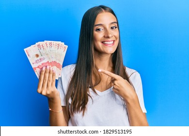 Young hispanic woman holding colombian pesos smiling happy pointing with hand and finger