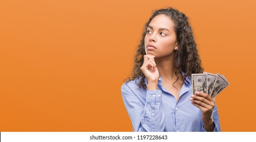 Young hispanic woman holding dollars serious face thinking about question, very confused idea