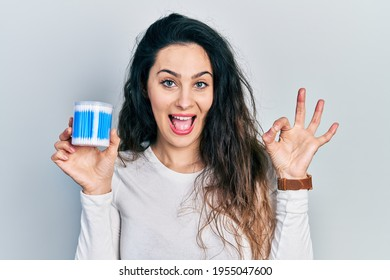 Young hispanic woman holding earwax cotton remover doing ok sign with fingers, smiling friendly gesturing excellent symbol