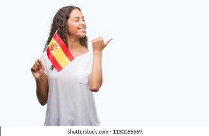 Young hispanic woman holding flag of Spain pointing and showing with thumb up to the side with happy face smiling